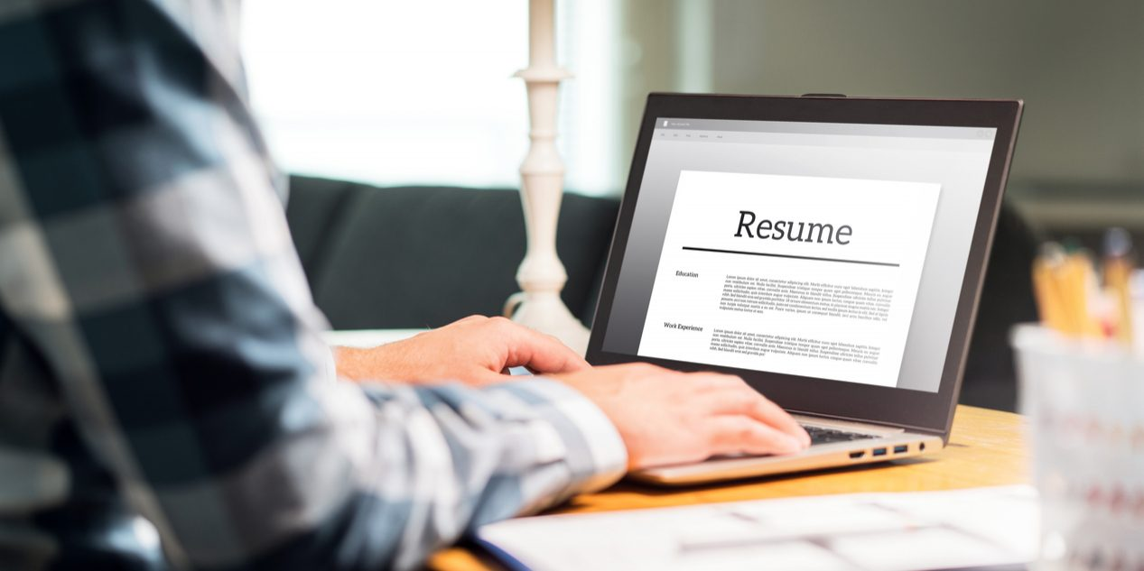 Man writing resume and CV in home office with laptop. Applicant searching for new work and typing curriculum vitae for application. Job seeking, hunt and unemployment. Mock up text in computer screen.