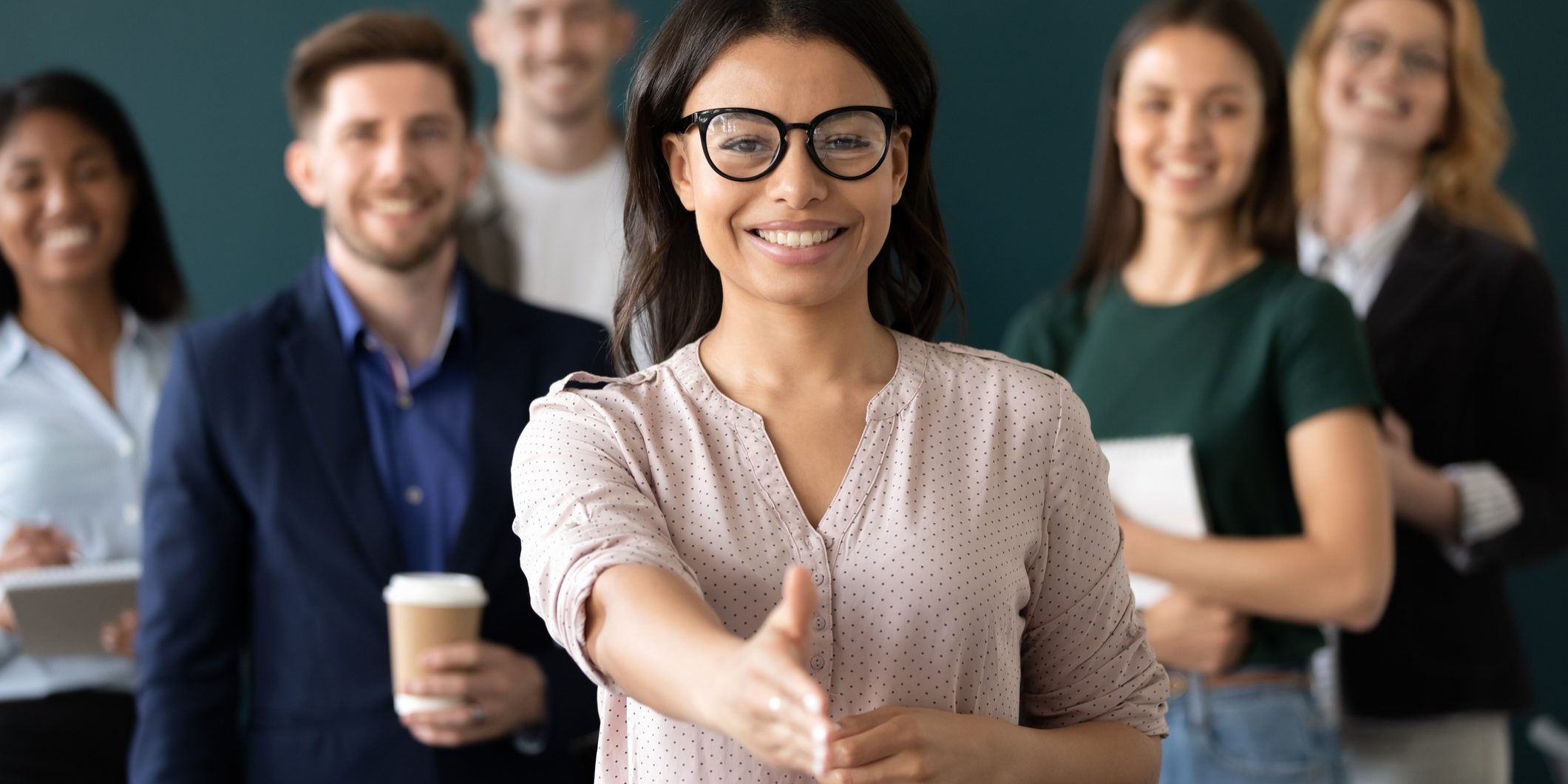 Mixed race woman sales manager stretch out hand introduces herself greeting shake hands client smiling look at camera pose indoors with diverse teammates. HR, job interview, business etiquette concept