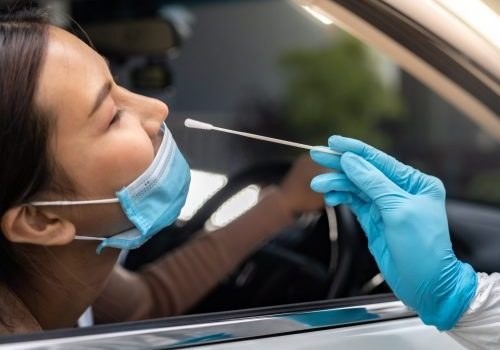 Portrait of asian woman drive thru coronavirus covid-19 test by medical staff with PPE suit by nose swab.